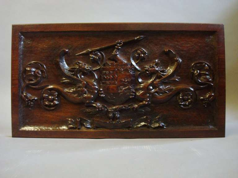 Late C19th carved walnut armorial panel, the central shield with a raised arm clenching a spear, the shield incorporating various emblems including a crouching lion, winged eagles, plume of feathers; flanked by a pair of opposing griffins and