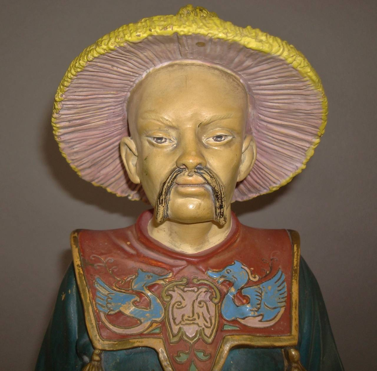 A 19th century decorated terracotta chinaman, retaining its original colourful polychrome decoration; his traditional oriental costume with straw coollie hat and robe finely decorated with butterflies, birds and foliage; carrying two rectangular