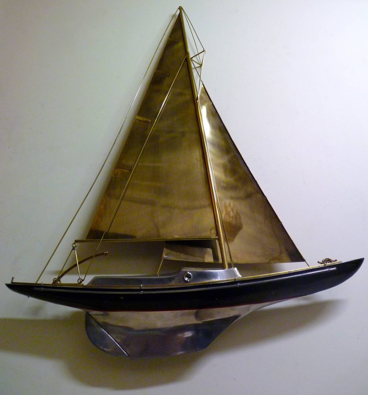 Sailboat wall sculpture by Curtis Jere in cast aluminum and patinated brass. This piece is signed as shown and dates to the 1980s. This particular Jere sculpture is likely the highest quality construction of any Jere sculpture that I have seen yet.