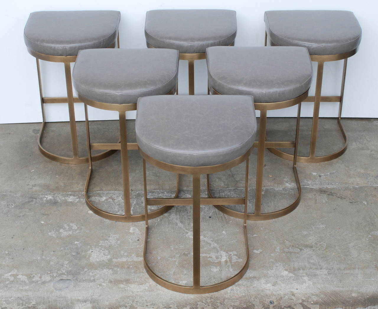 These flat bar Milo Baughman bar stools have been replated in a beautiful burnished brass which involves a high level of hand polishing. The seats have been recovered in luxurious Italian gray leather. These are in mint condition.