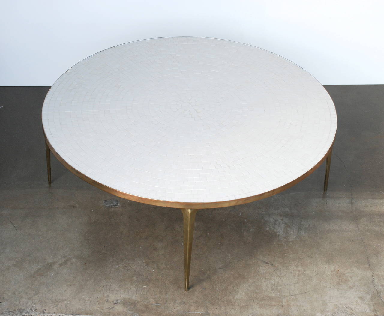 A beautiful table with pointed brass legs that are stamped made in japan the white
