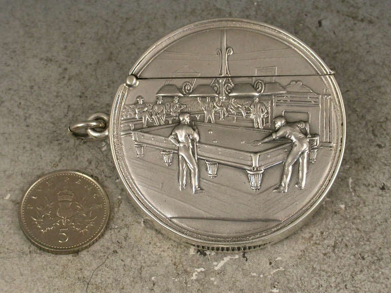 A very rare Edwardian documentary circular silver Vesta case of large size with hinged flip-top lid, the face chased and engraved with a billiards room, two players at the table, spectators and a score board in the background, a striker to the base.