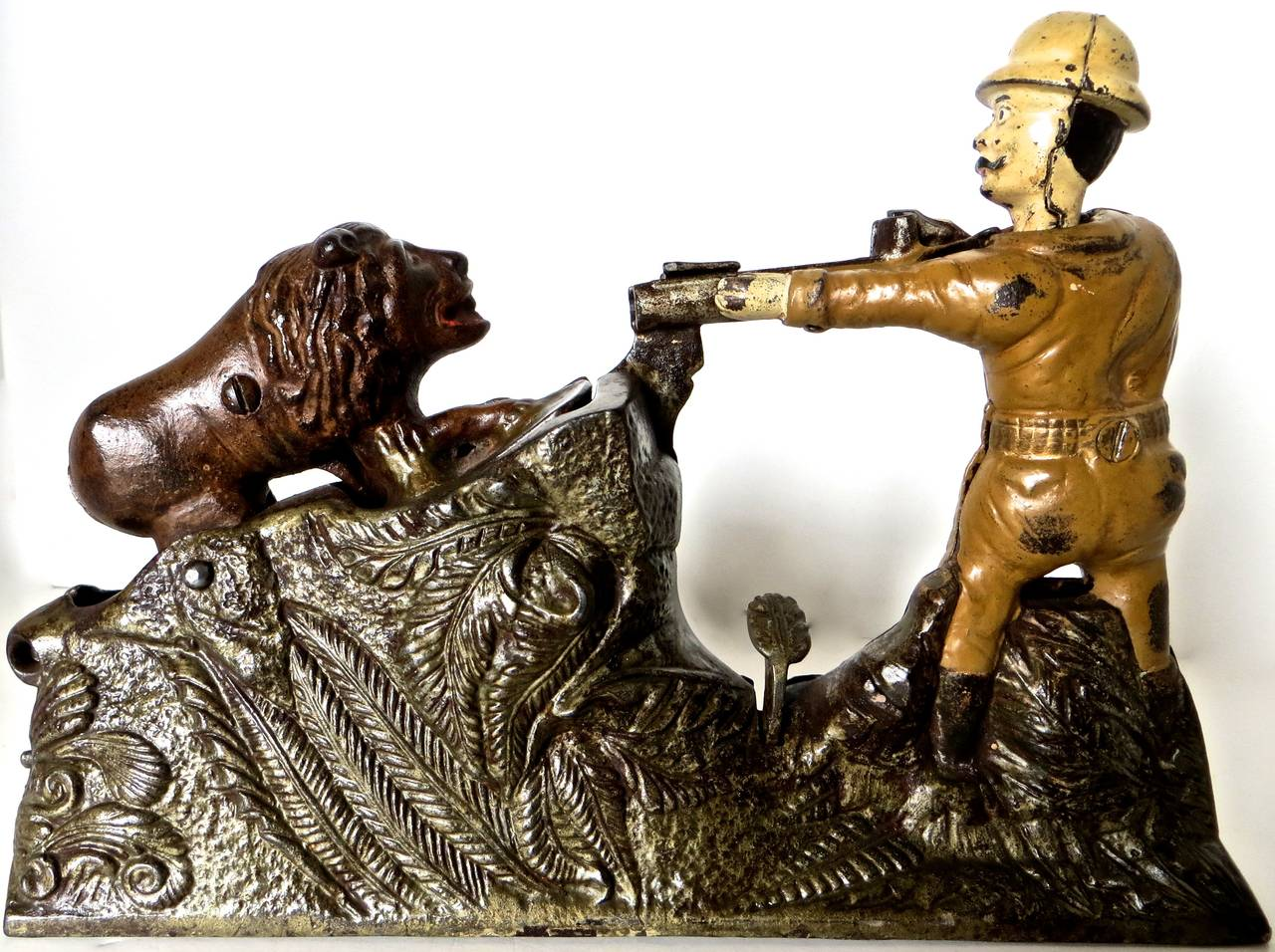 Manufactured in 1911 by the J. & E. Stevens Company in Cromwell, Connecticut, this cast iron mechanical bank depicts President Teddy Roosevelt aiming his rifle at a lion. Roosevelt is well-known for his affinity towards big game hunting, and