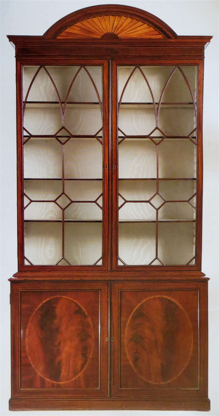 The highlight of this inlaid mahogany cabinet from the late 18th century is the arched pediment with sunburst fan like veneers which exhibits a three dimensional appearance. Below are two glazed doors crossbanded with ebony and boxwood, with