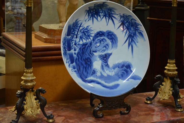 A charming very fine large Japanese porcelain charger. The thickly potted porcelain charger with underglaze landscape decoration, a Korean stylized tiger in landscape of graceful bamboo, unmarked. Stand not included.  Provenance: Assembled from our