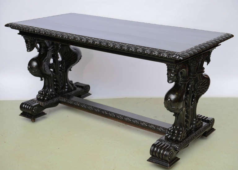To The Manor Born-an extraordinary table to distinctively enrich any space, as a center table or writing table. Richly carved caryatid side supports surmount a carved scroll stretcher base terminating in raised plinth supports. A marvelous ebonized
