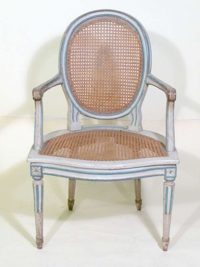 Very fine sophisticated Duchess Marguerite de Rothschild style pair of 18th century French Louis XVI armchairs-oval balloon backs with cane back and seat, scrolled arms, and fluted legs standing on turnip feet, retaining original faded white painted