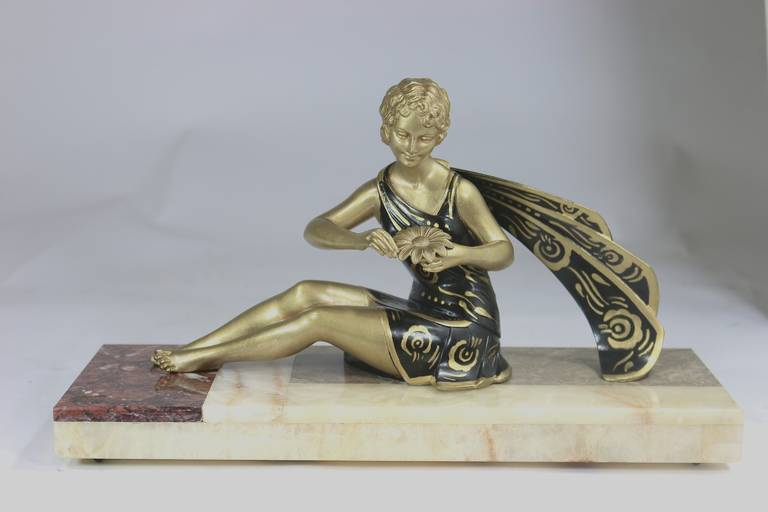 Beautiful Art Deco black and gold sculpture of seated woman playing with flower petals the love game 'He Loves Me, He Loves Me Not' recently restored finish. Dressed in a lovely dress and scarf on an onyx and marble base. A charming 1930s designed