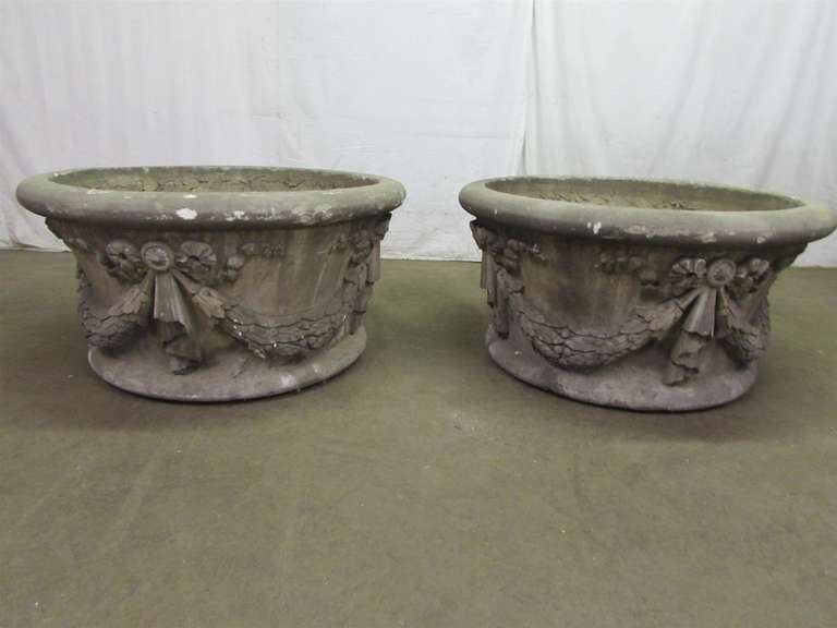 These urns were salvaged from an old building in New York. These have crackling throughout and obviously have been around a while. Beautiful design and large sized for your garden setting. Made of cement with a floral wreath. These can be seen at