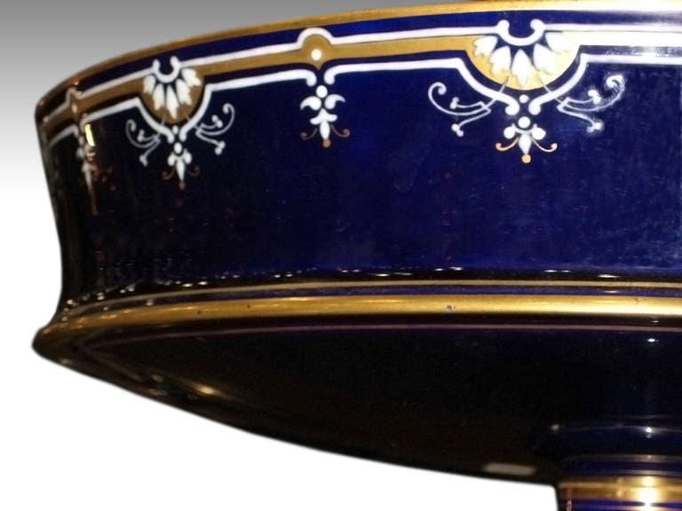 This is a beautiful fine porcelain tazza with gilt and enamel, signed 'Sevres,' from France. It is dated 1890, as suggested on the underside with the number S87. Glazed in their famous 'Bleu Du Roi'. Minor scratches inside. This can be seen at our 5