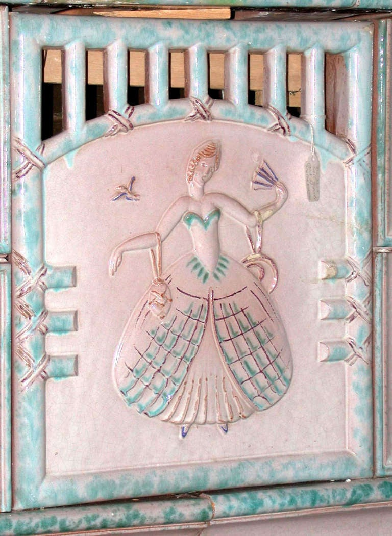 This is a beautiful 1800s tile mantel or tile stove, from Austria. It is made of pink tiles with an aqua border; each tile has a motif of different scenes, a house, a man in front of a tree, and a large one in the center of an elegant lady from the