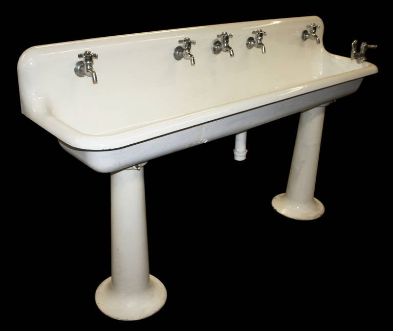 industrial porcelain gang sink on pedestal legs without