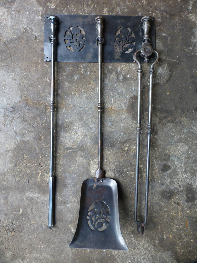 Th century polished steel fireplace tool set and hanger