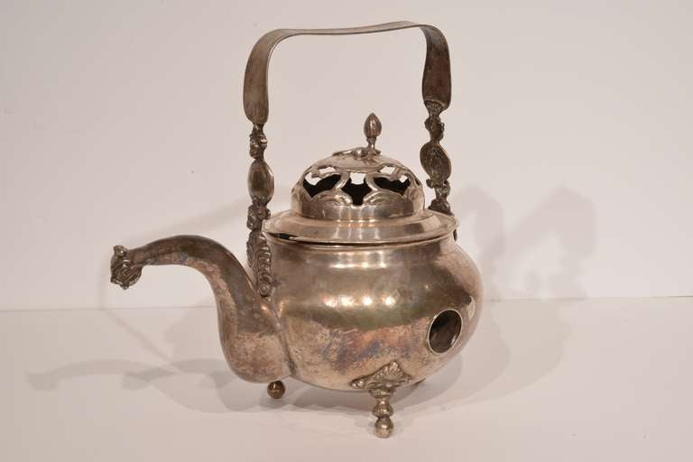 Fine silver chocolate pot from Bolivia. This piece rests on three delicate, foliate-detailed feet. Its spout is crafted into the form of a jungle cat. The pot features a flattened handle and a punched-out, separate top.