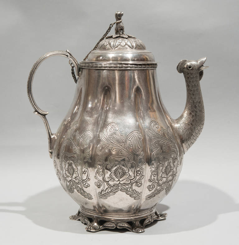 This silver cafeteria from Bolivia features floral and foliage decoration. It also features a bird-head spout, a dog with leash finial, carved gadrooned handles, and cast leaf scroll feet.