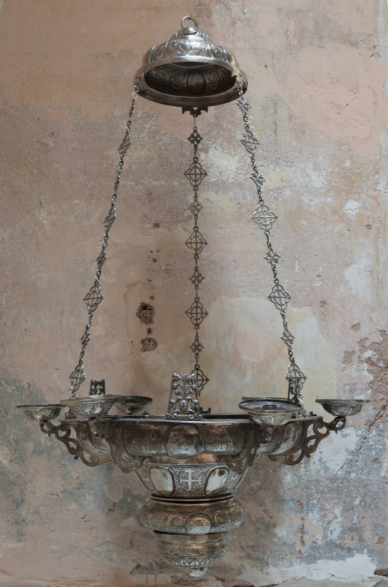 Spanish Colonial chandeliers were popular objects for devotional offerings. This chandelier is unsigned and its design features prominent crosses. This suggest that it may have been commissioned by or for a church. The overall design is primarily