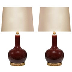 Pair of Copper Red Glazed Porcelain Lamps with Gilt Bronze Bases