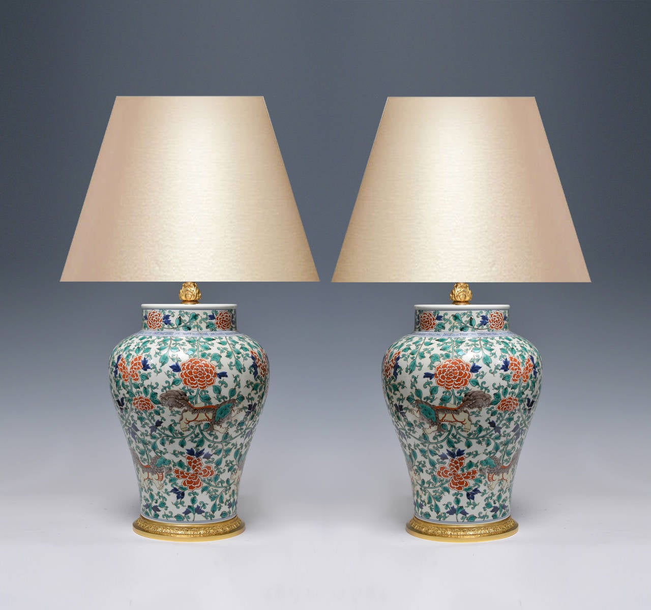 Pair of fine painted pink background famille verte porcelain lamps with fine cast gilt bronze bases, with foo lions and flower blossom decoration. (Lampshade not included).