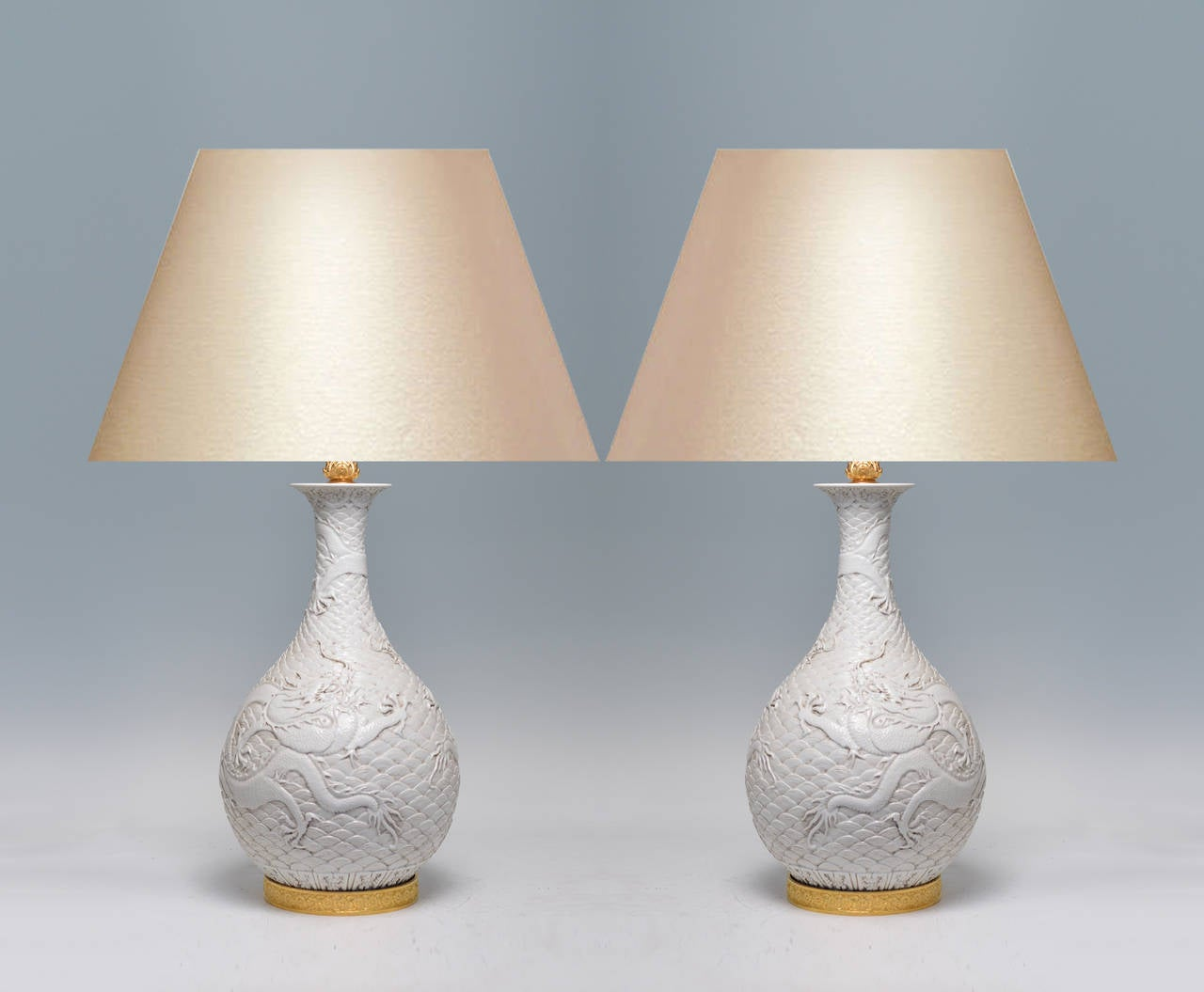 Fine carved white porcelain vases decorated with dragons surrounded by clouds, Gilt bronze bases. To the porcelain: 20.5