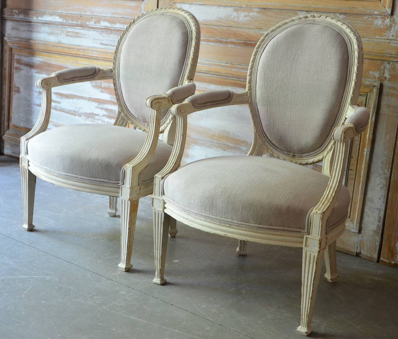 A pair of 19th century Louis XVI style Cabriolet armchairs, medallion back with elegant knotted-ribbon motifs, fluted arms, carved apron and corner blocks on turned tapering legs in worn cream patina. Upholstery in palest grey linen.