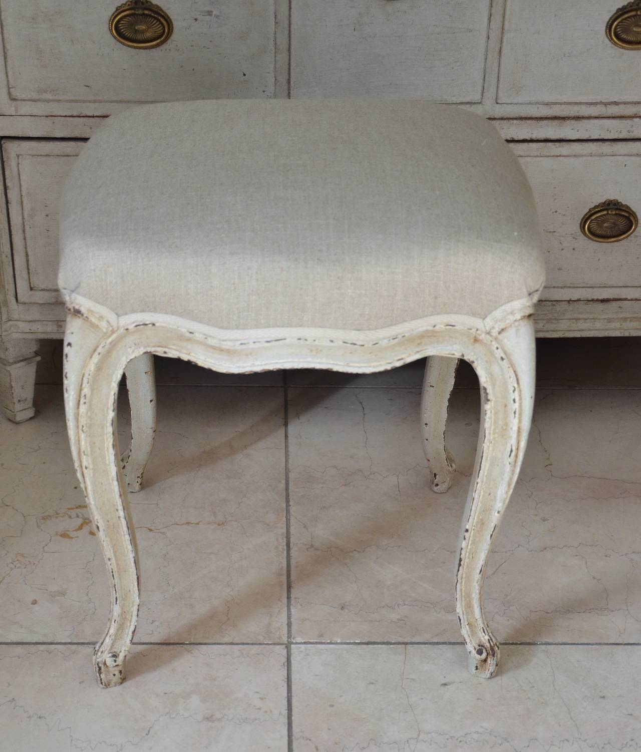 A pair of small footstools in Louis XV style with scalloped frieze carved and  raised on cabriole legs. Newly upholstered in linen.
