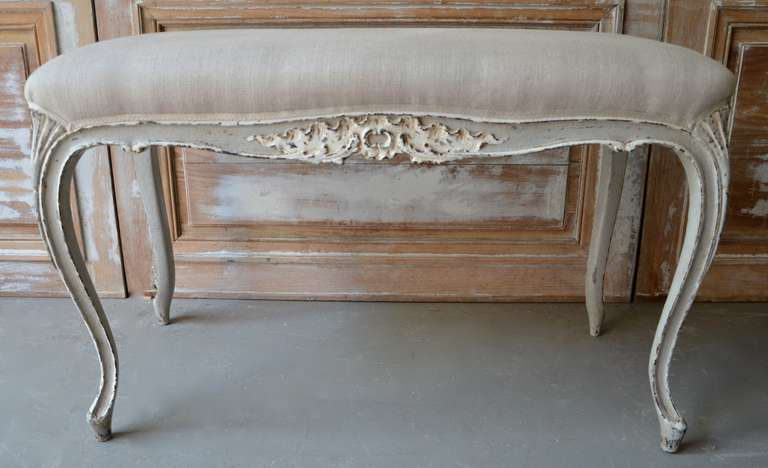 A small bench in Louis XV style with scalloped frieze carved in floret motifs, raised on cabriole legs. Upholstered in linen.