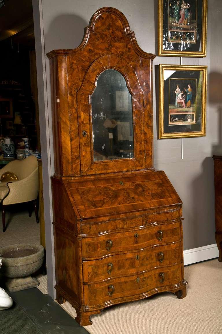 An early 18th century Italian Venetian walnut and burl walnut veneered secretary with serpentine base and mirrored upper door.
