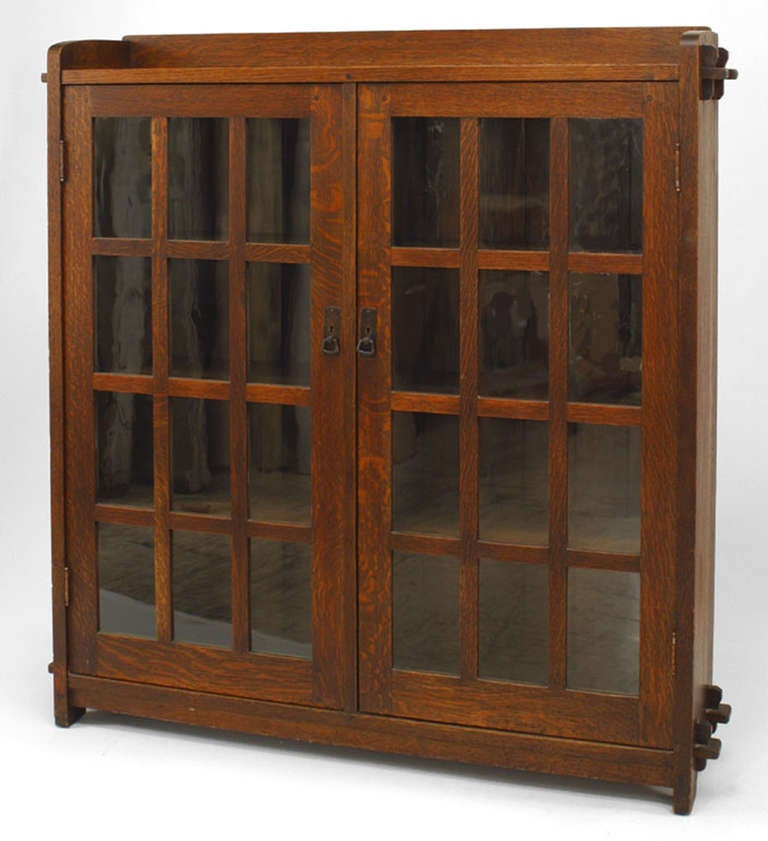 American Mission oak bookcase with four shelves and a facade comprised entirely of a pair of glass doors each finished with iron hardware and divided into twelve panes beneath a rectangular galleried top. The piece bears a red label which identifies