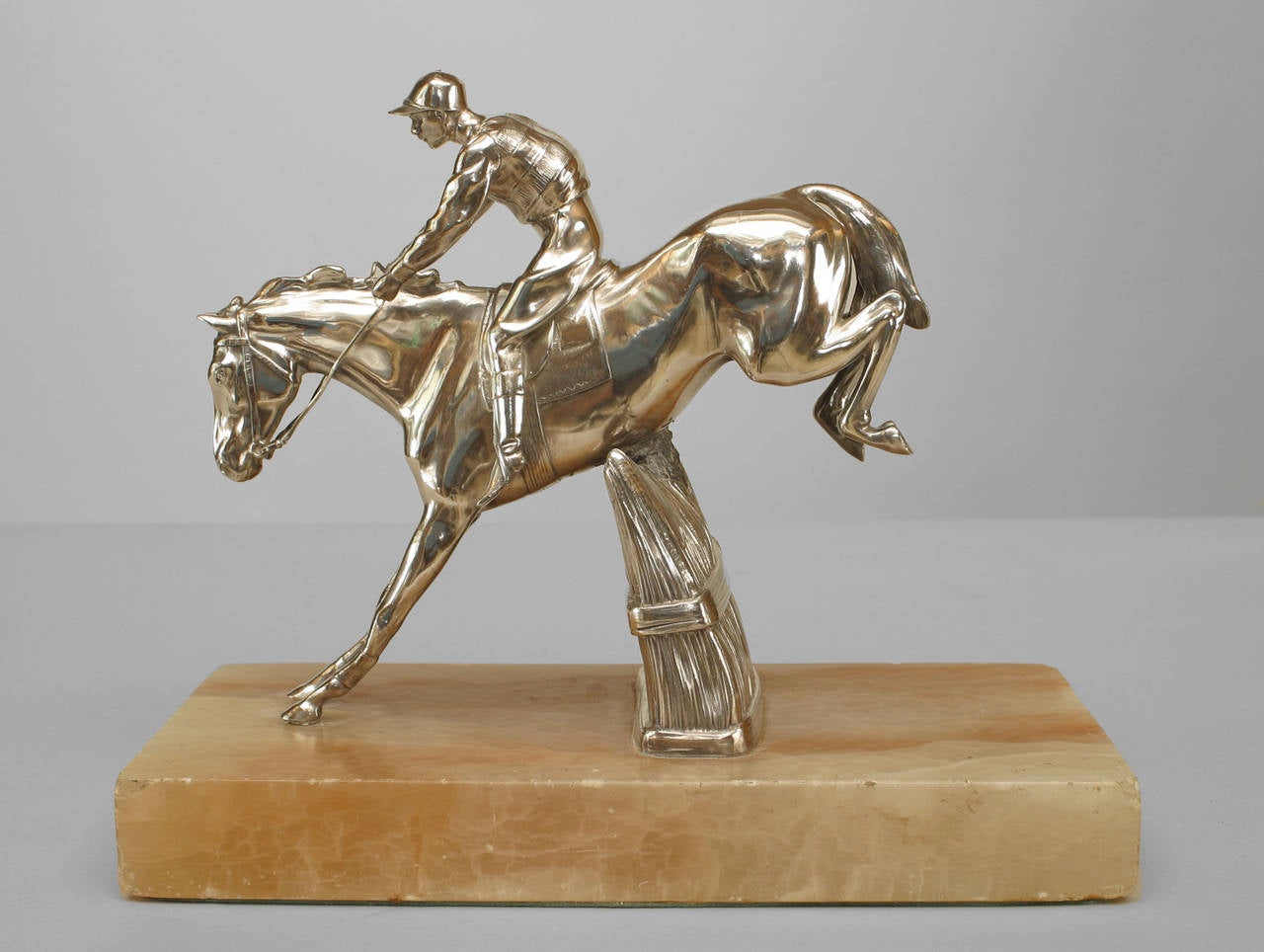 Nineteenth century English silver-plated bronze figure of horse and jockey jumping a grass fence on a rectangular white onyx base.