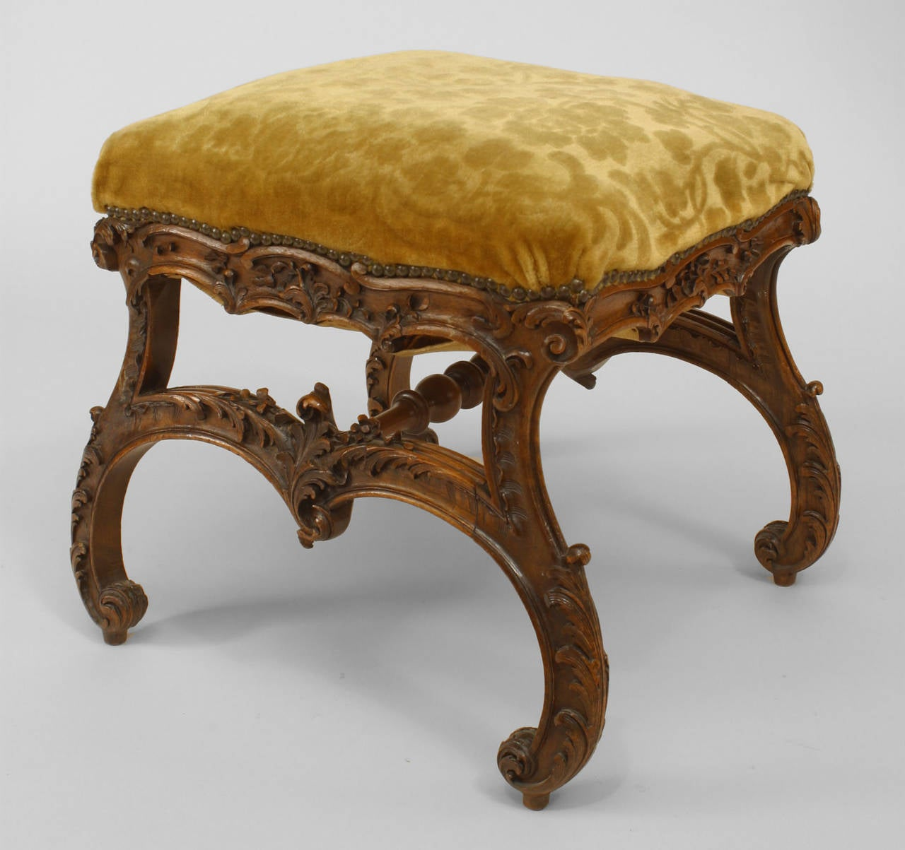 19th century Italian Baroque style walnut square bench with scroll form legs connected with a replaced stretcher and a gold velvet upholstered seat.