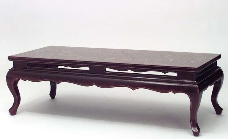 Twentieth century Chinese rectangular coffee table with a shaped apron and four cabriole legs. The piece is composed of maroon lacquered bamboo decorated with gilt trim.