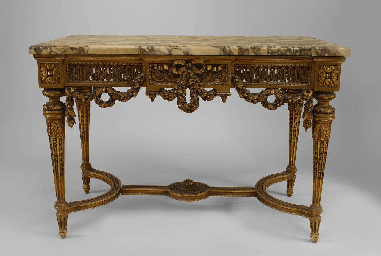 19th century French Louis XVI style gilt center table with a stretcher, marble top, and open filigree apron with swag carving.