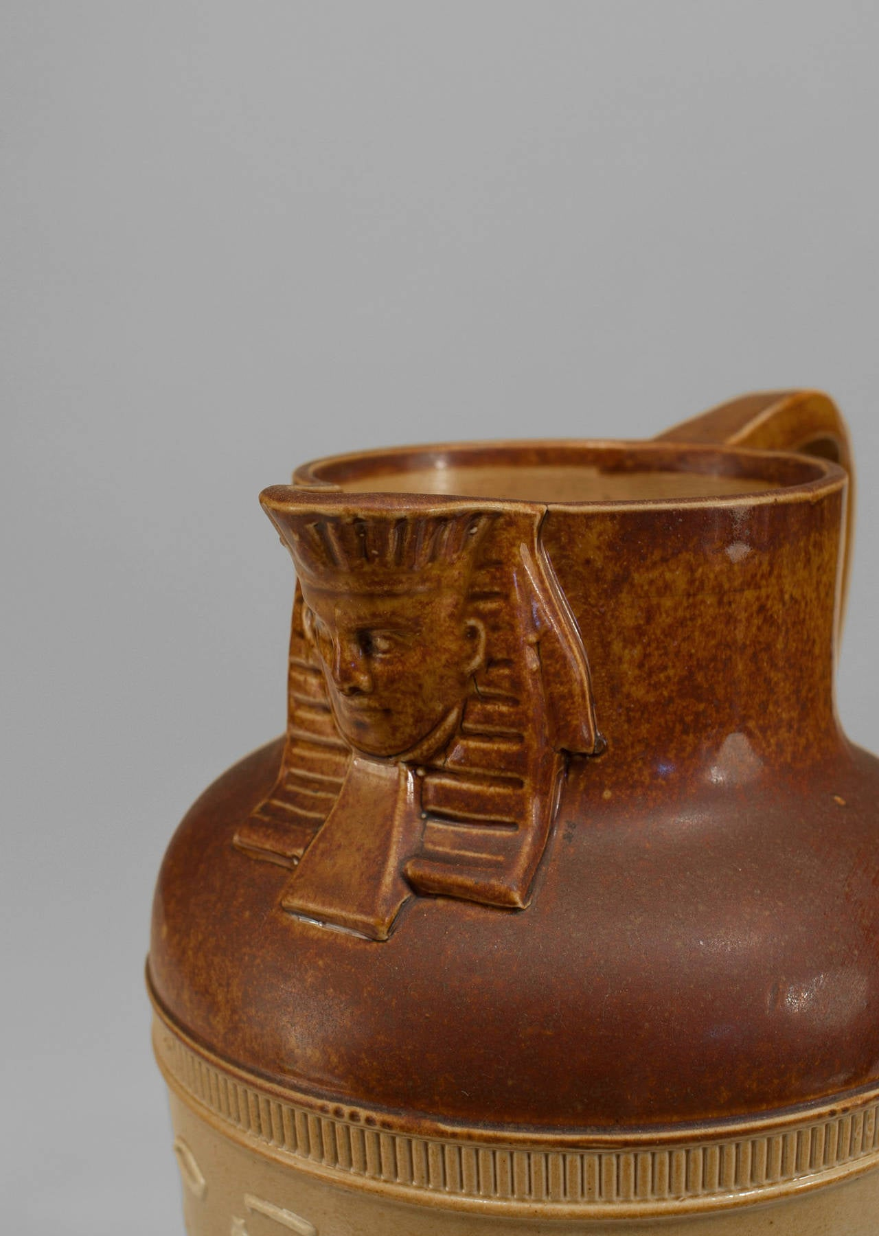 1920's English small brown pitcher with an pharaoh-headed spout sphinx and beige and white classical figures in relief. Impressed