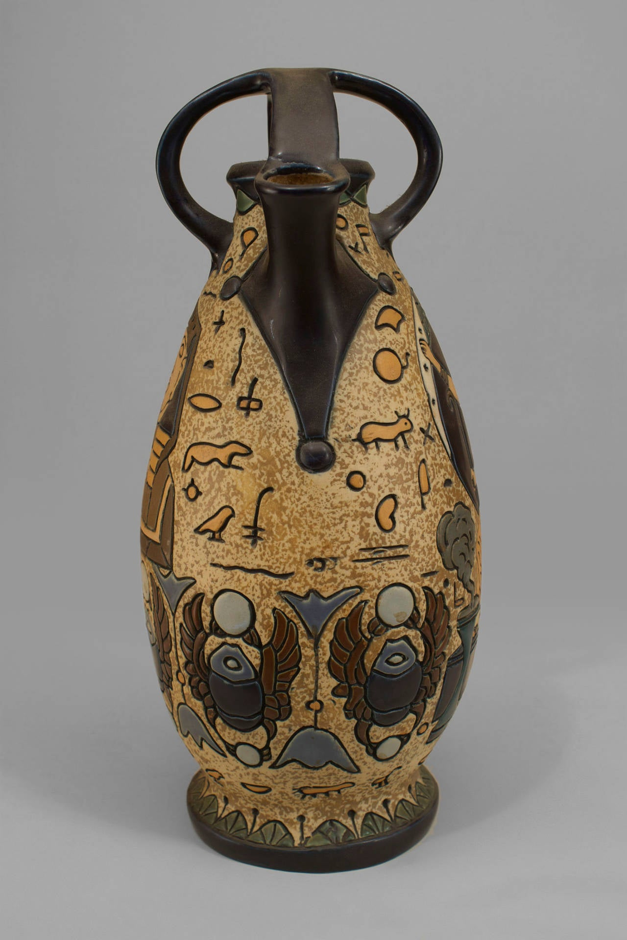 Early 20th century amphora of probable Czechoslovakian origin. The vase is decorated with Egyptian Revival figures and motifs and is trimmed in black with a spout and open cage top.