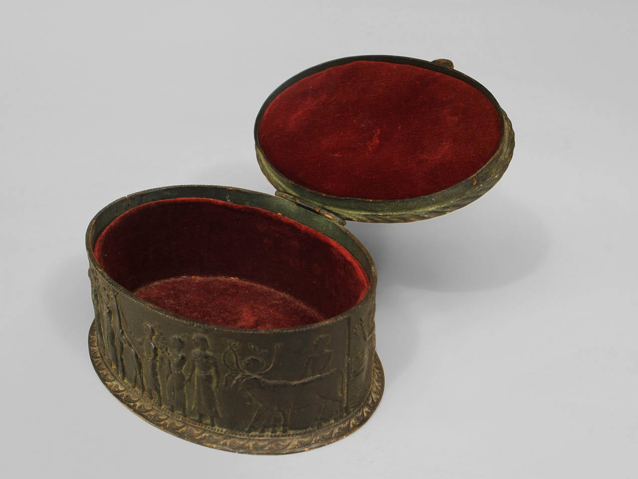 Egyptian Revival Style box of probable late 19th century French origin. The oval box is cast from dark bronze and decorated with classical figures in relief in addition to a scarab and 2 stones at the top.