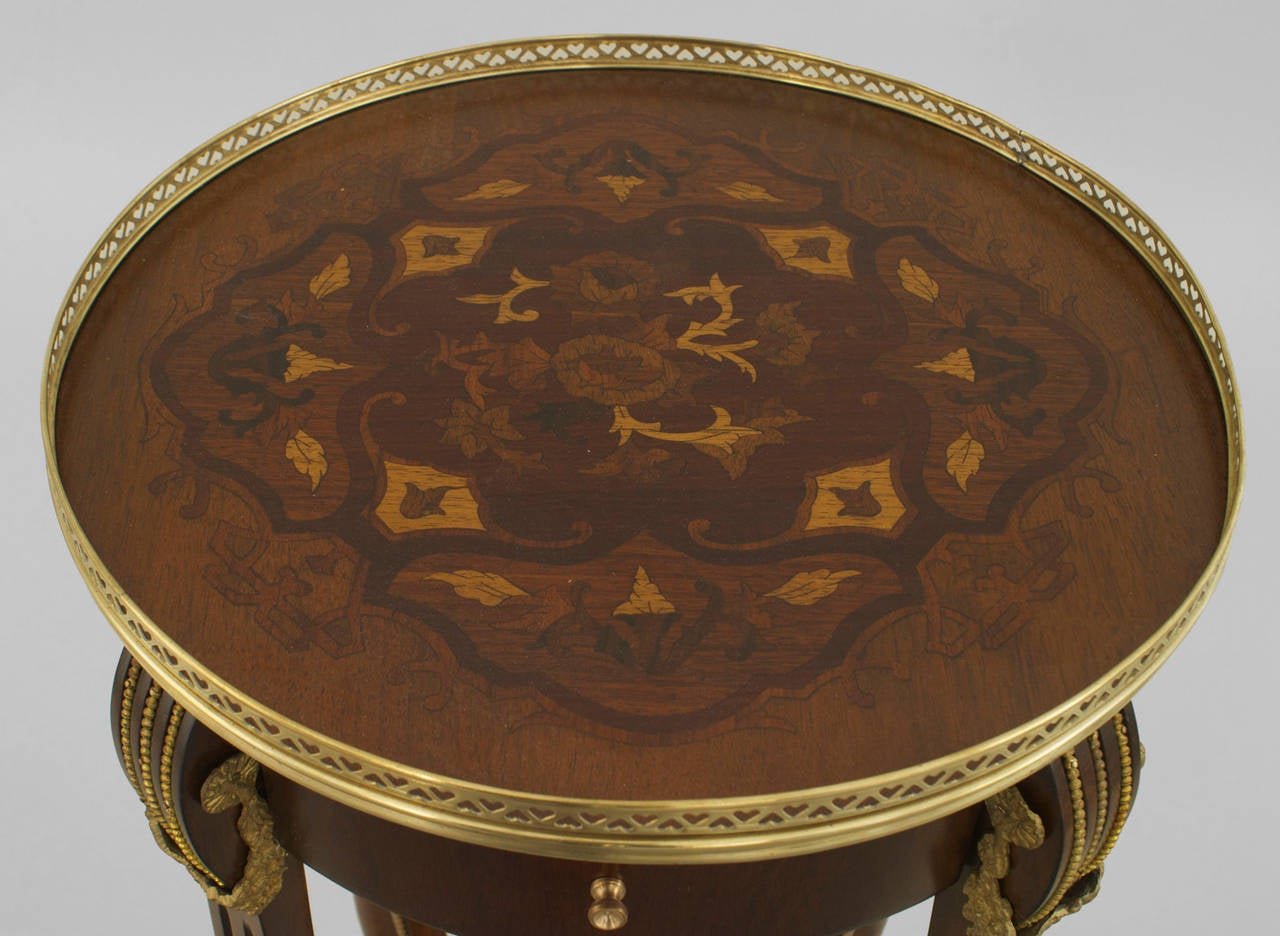 Pair of turn of the century French Louis XVI style round end tables with floral inlaid tops having brass filigree galleries and shelves with bronze baskets and trim.