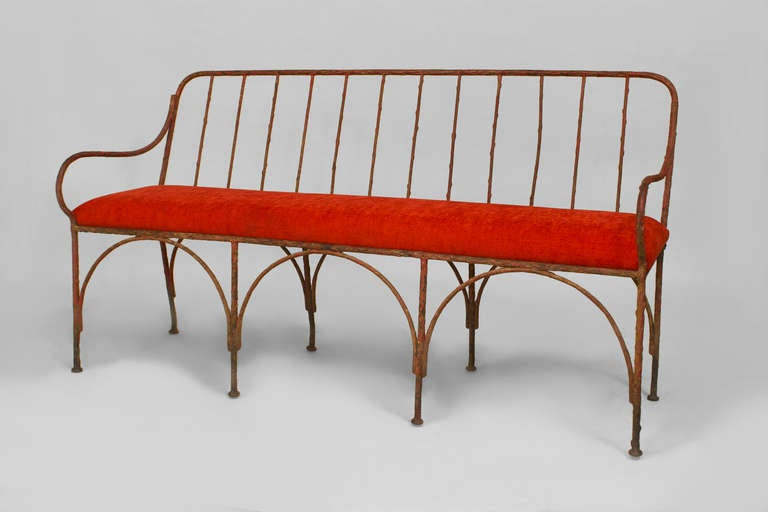 French Art Moderne bench dating to the 1930s or 1940s. The wrought iron bench features a red upholstered seat supported by a linear, spindle design back with open arms and eight legs joined by two rows of arcaded stretchers.