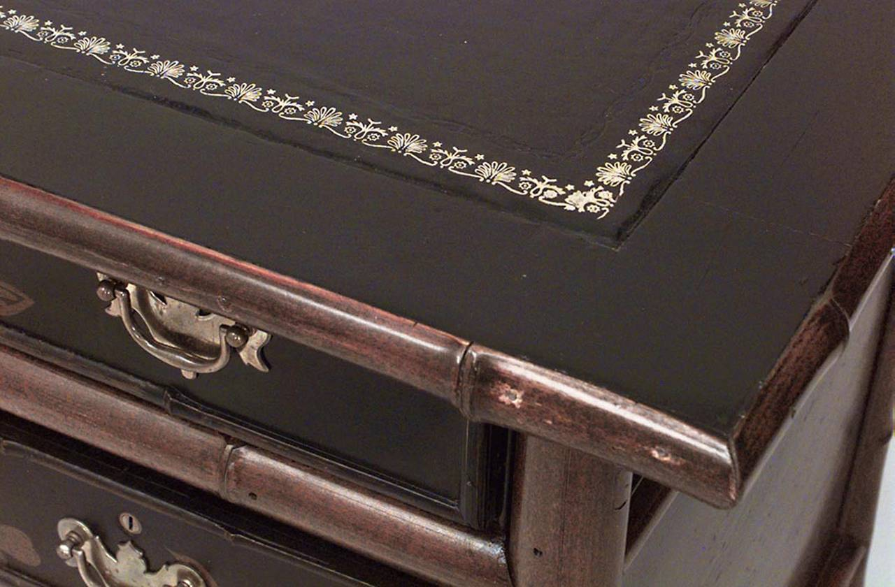 19th century English and black lacquered chinoiserie decorated desk with a black leather top and drawers on one side.