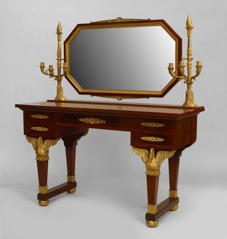 Nineteenth century French Empire mahogany dressing table featuring five drawers, gilt bronze ornamentation, swan-form leg supports, and an octagonal mirror bolstered by a pair of candelabra.