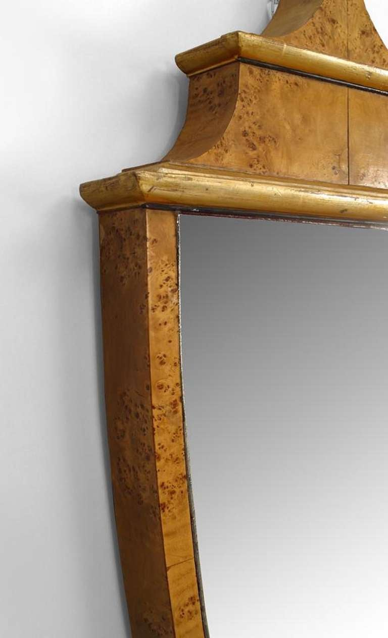Dating to the 1930's, this pair of Italian mirrors is crafted from karelian birch and takes an elongated, urn-shaped Neoclassic style form that is accented with gilt trim.