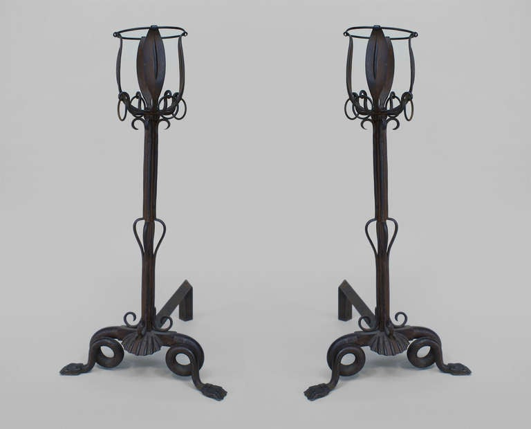 Pair of French Art Nouveau iron andirons formed in imitation of long-stemmed flowers or baskets supported by claw foot bases decorated with scrolls and seashells.