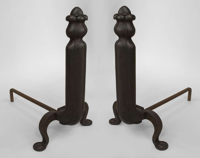 Pair of American Art Nouveau iron andirons with foliate finials over a fluted shaft design.