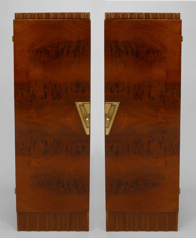 Pair of French Art Deco mahogany veneered pedestal cabinets with fluted tops and bottom edges on either side of front doors finished with bronze geometric key plates that together form a trapezoidal keystone shape.
