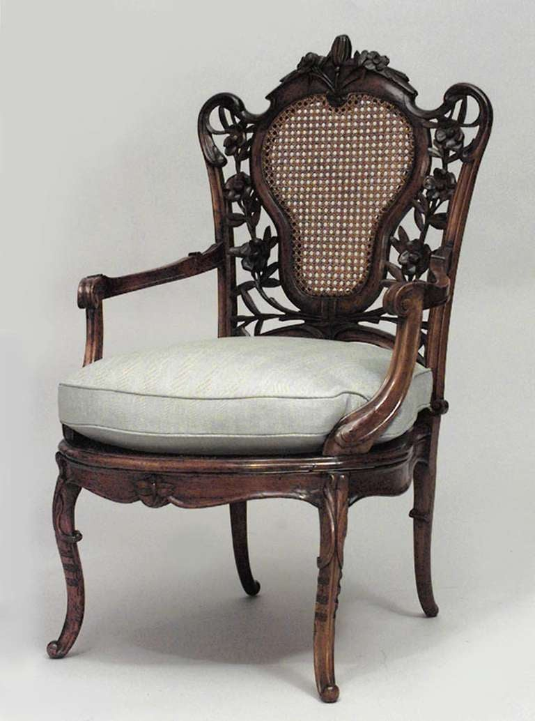 French Art Nouveau armchair composed of walnut carved with filigree around a cane panel back. The chair rests upon four curved legs, has a seat cushion upholstered in grey fabric, and features carvings drawn from nature, such as flowers and insects,