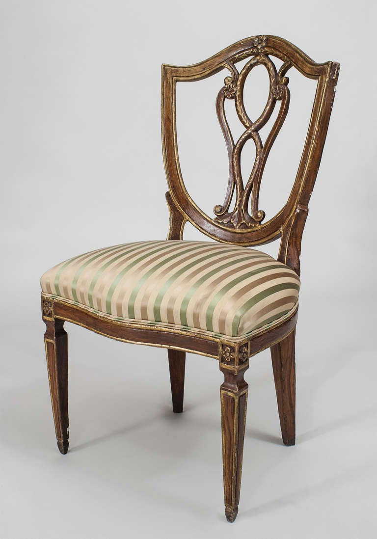Italian Neo-classic style (19th Cent) brown painted and gilt trimmed side chair with oval open carved shield form back and striped upholstered seat.