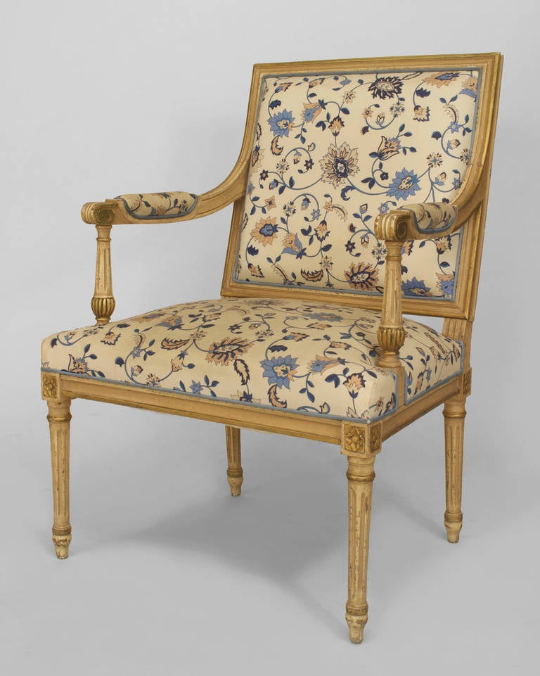 Twentieth century Louis XVI style white-painted and gilt-trimmed open arm chair with a square back and seat carved with classicizing details and upholstered in blue and white floral fabric.
