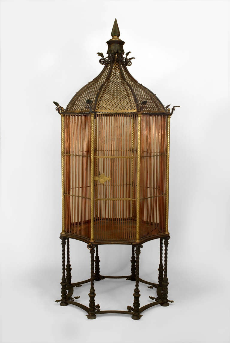Nineteenth century English monumental birdcage composed of bronze and copper bars arranged in an octagonal form and crowned with a pierced gilt dome and finial top, all mounted upon a base of eight conjoined swirled iron legs. The piece holds the