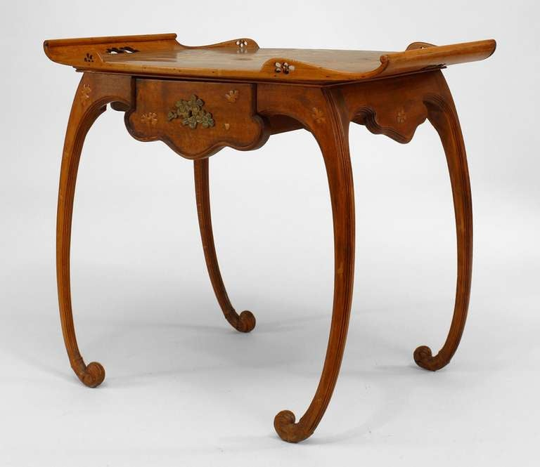 French Art Nouveau serving table signed by Emile Galle. The table is composed of walnut decorated with inlaid and incised floral designs and rests upon four convex scroll legs beneath a tray-form top with filigree gallery corners and a drawer.