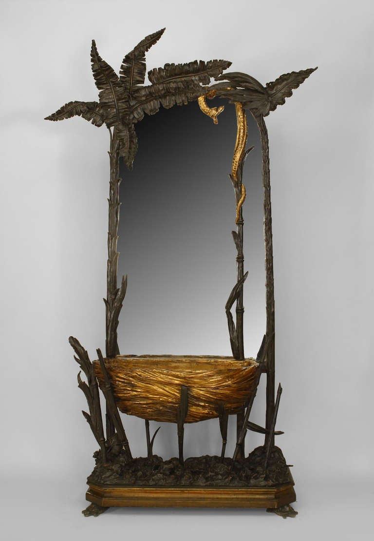 French Napoleon III oval cheval mirror set within a naturalistic frame and stand composed of carved wood in the form of palms and ferns. A carved gilt basket planter lies beneath the mirror and a coiled gilt snake bisects the mirror, further