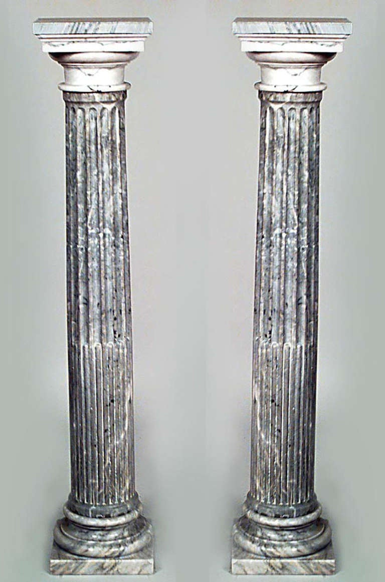 Pair of French Louis XVI style columns composed of grey marble with square tops as well as fluted shafts and circular bases reminiscent of the classical ionic order.